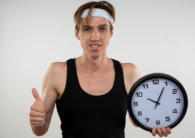 白で隔離の親指を示す壁時計を保持しているヘッドバンドとリストバンドを身に着けている若いスポーティな男の笑顔