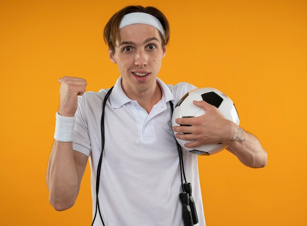 Smiling young sporty guy wearing headband with wristband with jump rope on shoulder holding ball