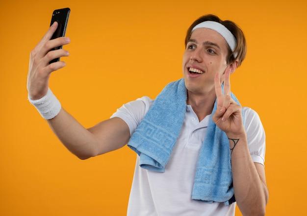 Il giovane ragazzo sportivo sorridente che indossa la fascia e il braccialetto con l'asciugamano sulla spalla prende un selfie punti in alto isolato sulla parete arancione