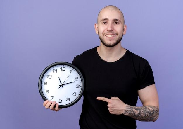 Sorridente giovane uomo sportivo holding e punti all'orologio da parete isolato sulla porpora
