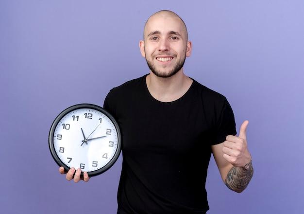Sorridente giovane uomo sportivo tenendo l'orologio da parete il pollice in alto isolato su viola