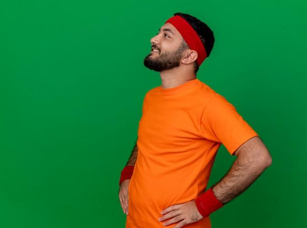 コピースペースと緑の背景で隔離の腰に手を置くヘッドバンドとリストバンドを身に着けている側を見て笑顔の若いスポーティな男