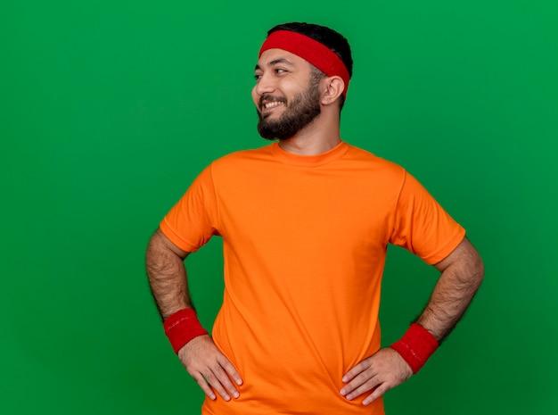 緑の背景で隔離の腰に手を置くヘッドバンドとリストバンドを身に着けている側を見て笑顔の若いスポーティな男