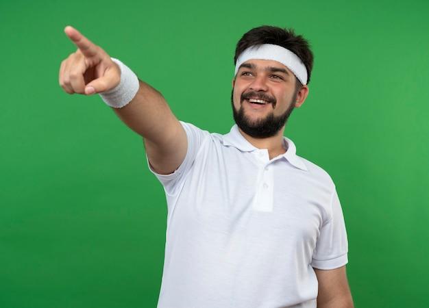 Sorridente giovane uomo sportivo guardando al lato che indossa la fascia e il braccialetto punti sul lato isolato sulla parete verde