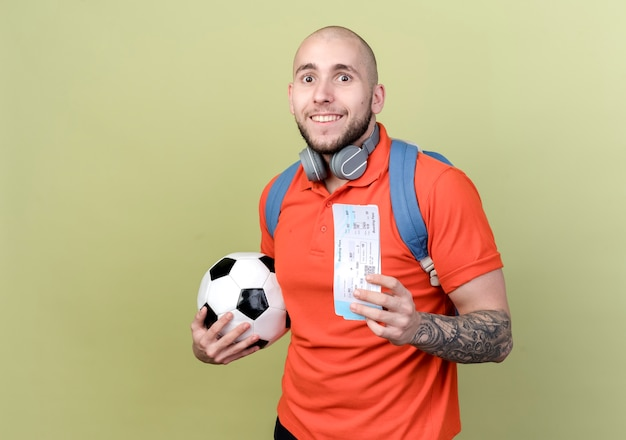 コピースペースとオリーブグリーンの壁に分離されたチケットとボールを保持している首にバックバッグとヘッドフォンを身に着けている若いスポーティな男の笑顔