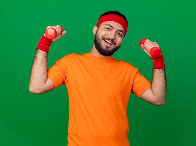 Улыбающийся молодой спортивный мужчина с повязкой на голову и браслетом, тренирующимся с гантелями, изолированными на зеленом фоне Бесплатные Фотографии