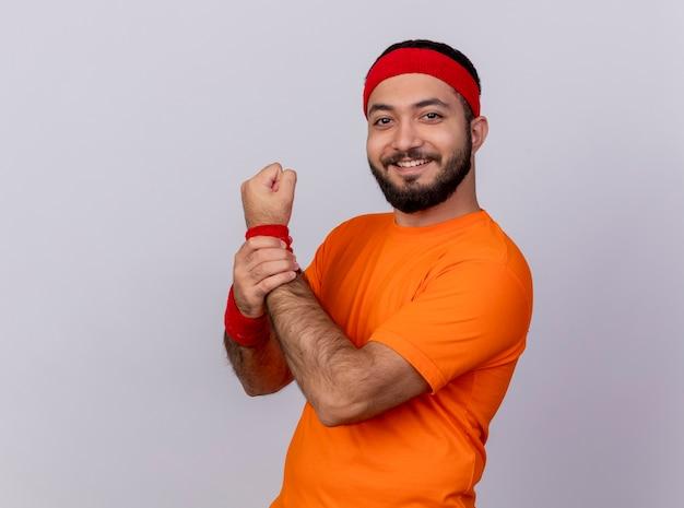 Улыбающийся молодой спортивный мужчина с повязкой на голову и браслет схватил его за руку, изолированную на белом