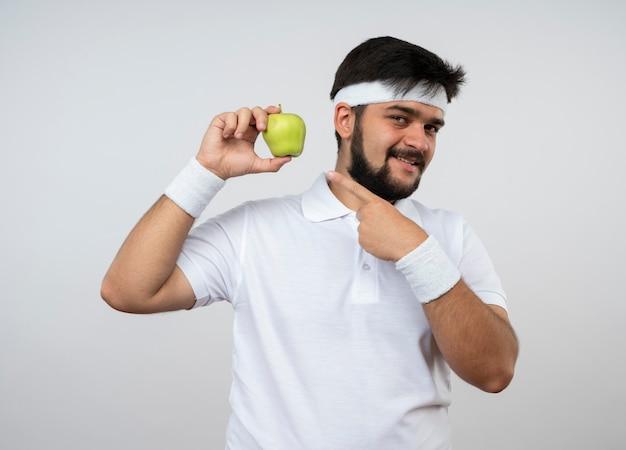 Улыбающийся молодой спортивный мужчина с повязкой на голову и браслетом держит и указывает на яблоко, изолированное на белой стене