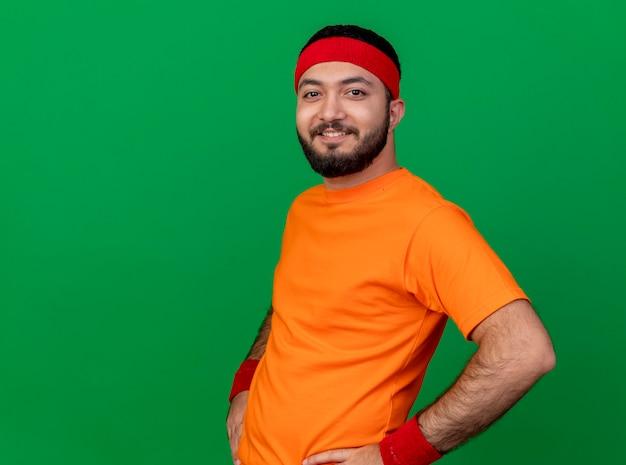 コピースペースで緑の背景に分離された腰に手を置くヘッドバンドとリストバンドを身に着けている若いスポーティな男の笑顔