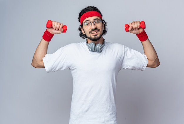 Улыбающийся молодой спортивный мужчина в головной повязке с браслетом и наушниками на шее, тренируясь с гантелями