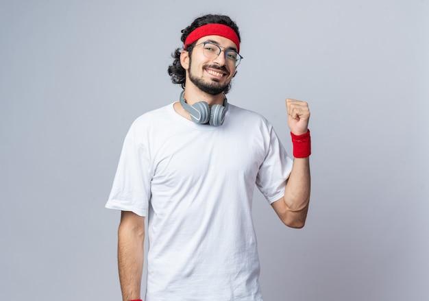 Улыбающийся молодой спортивный мужчина в головной повязке с браслетом и наушниками на шее, показывая жест