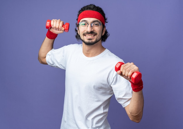 Улыбающийся молодой спортивный мужчина в головной повязке с браслетом, тренирующимся с гантелями