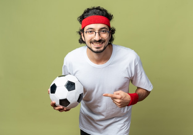 Улыбающийся молодой спортивный мужчина в головной повязке с браслетом и указывает на мяч