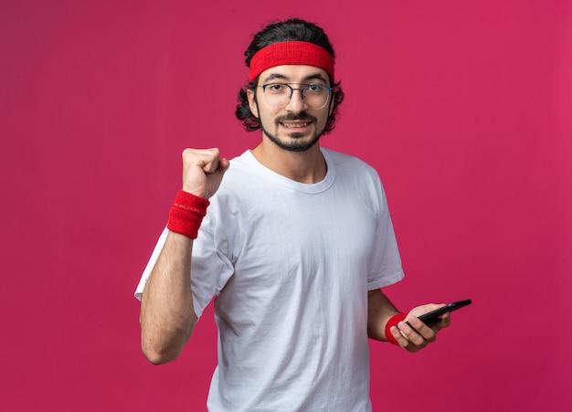 예 제스처를 보여주는 전화를 들고 팔찌와 머리띠를 착용 웃는 젊은 스포티 한 남자