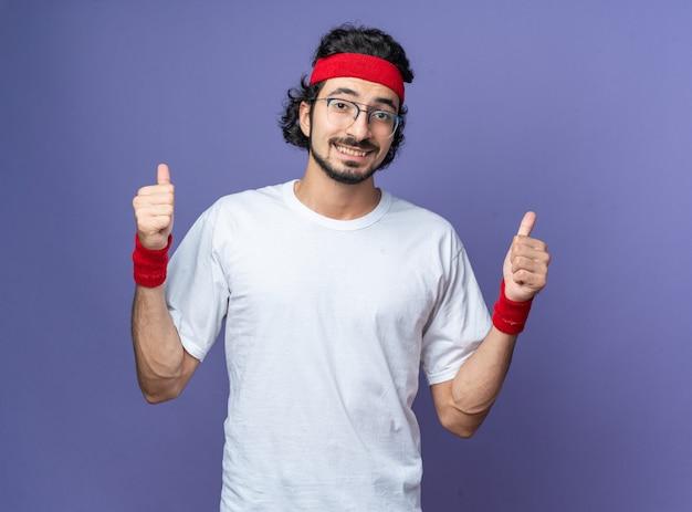 엄지손가락을 보여주는 팔찌와 머리띠를 착용 웃는 젊은 스포티 한 남자