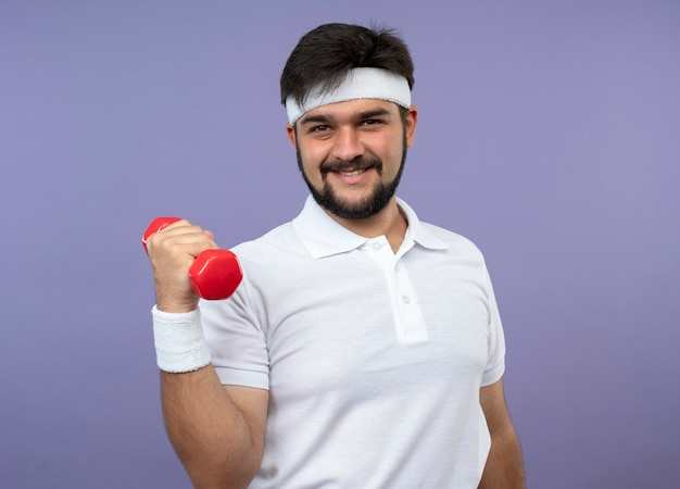 Smiling young sporty man wearing headband and wristband exercising with dumbbell