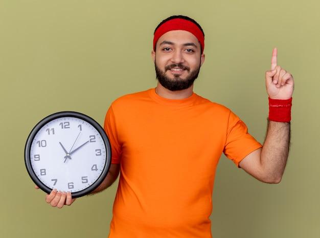 Sorridente giovane uomo sportivo che indossa la fascia e il braccialetto che tiene l'orologio da parete e indica in alto isolato su sfondo verde oliva