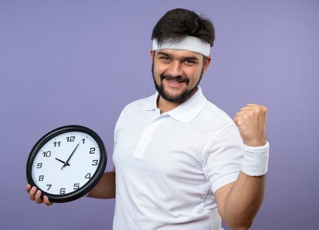 Sorridente giovane uomo sportivo che indossa la fascia e il braccialetto che tiene l'orologio di parete che mostra sì gesto
