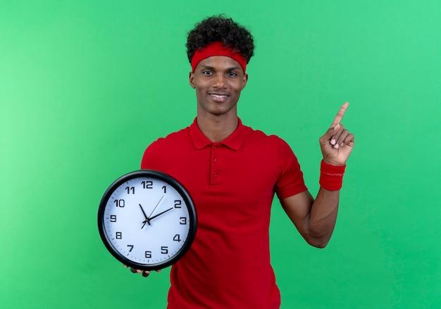 Sorridente giovane uomo sportivo che indossa la fascia e il braccialetto che tiene orologio da parete