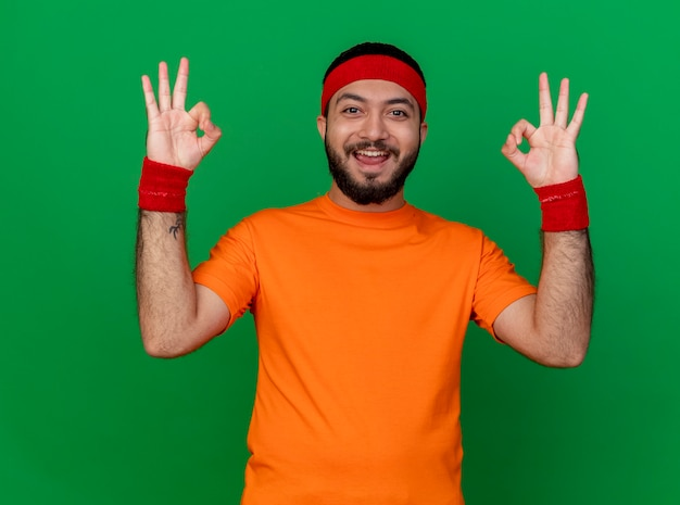 Smiling young sporty man wearing headband and wristband showing okay gesture isolated on green background