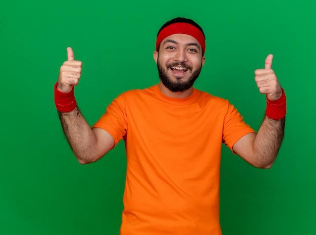Sorridente giovane uomo sportivo che indossa la fascia e il braccialetto che mostra i pollici in su isolato su sfondo verde