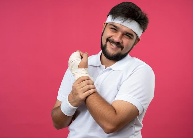 Sorridente giovane uomo sportivo che indossa la fascia e il braccialetto con il polso avvolto con benda afferrò il polso dolorante