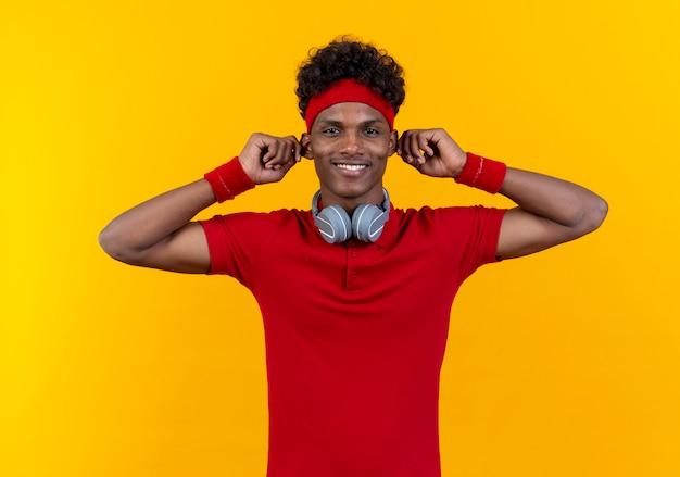 Sorridente giovane uomo sportivo che indossa la fascia e il braccialetto