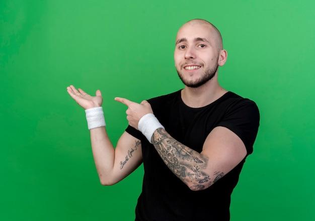 Улыбающийся молодой спортивный мужчина в браслете, притворяющийся, что держит, и указывает на что-то изолированное на зеленом