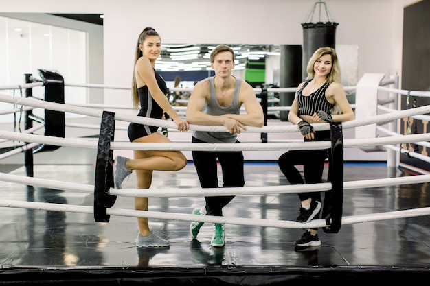 Smiling young sporty people, young mand and two girls, in sportswear in regular boxing ring in a gym