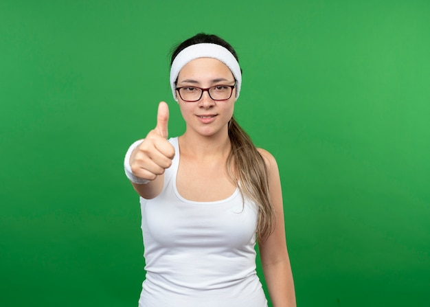 Sorridente giovane donna sportiva in vetri ottici che indossa la fascia e braccialetti pollici in su isolato sulla parete verde