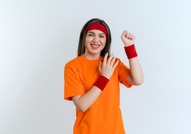 Smiling young sporty woman wearing headband and wristbands clenching fist looking keeping hand in air isolated