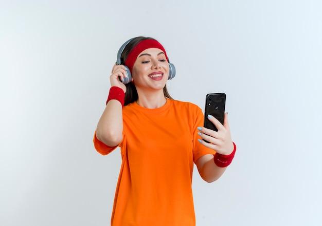 Sorridente giovane donna sportiva che indossa la fascia e braccialetti e cuffie tenendo e guardando il telefono cellulare afferrando le cuffie isolate