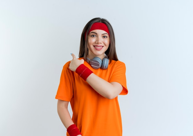 Smiling young sporty woman wearing headband and wristbands and headphones on neck looking pointing behind isolated