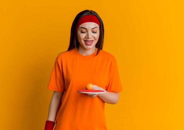 Sorridente giovane donna sportiva che indossa la fascia e braccialetti tenendo e guardando la racchetta da ping pong con pallina da ping pong su di esso