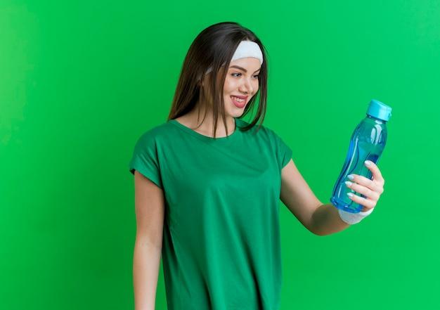 Sorridente giovane donna sportiva che indossa la fascia e braccialetti tenendo e guardando la bottiglia d'acqua
