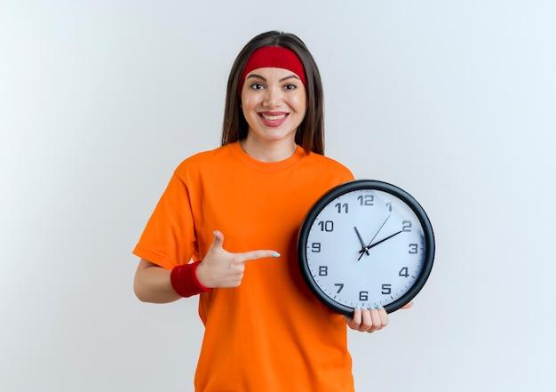 Sorridente giovane donna sportiva che indossa la fascia e braccialetti che tengono e che indica l'orologio isolato sulla parete bianca con lo spazio della copia