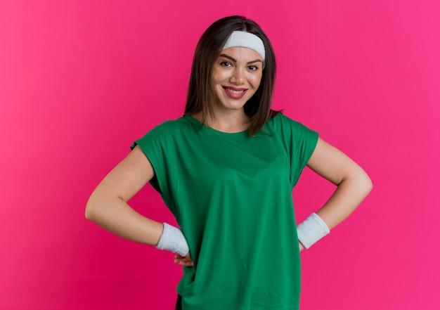 Sorridente giovane donna sportiva che indossa la fascia e braccialetti cercando di tenere le mani sulla vita