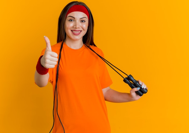 Smiling young sporty woman wearing headband and wristbands with jump rope around neck grabbing jump rope looking showing thumb up
