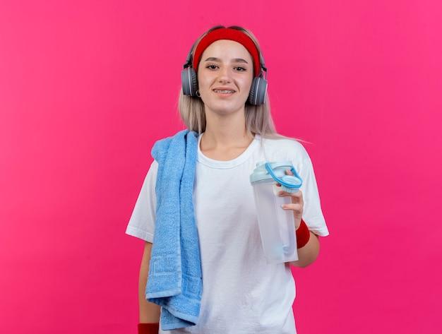 Улыбающаяся молодая спортивная женщина с подтяжками на наушниках, с повязкой на голову и браслетами держит бутылку с водой и полотенце на плече, изолированном на розовой стене