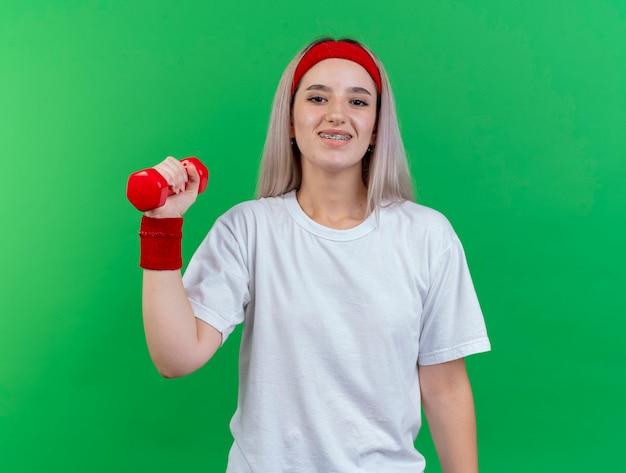 머리띠와 팔찌를 착용하는 중괄호와 웃는 젊은 스포티 한 여자는 녹색 벽에 고립 된 아령을 보유하고