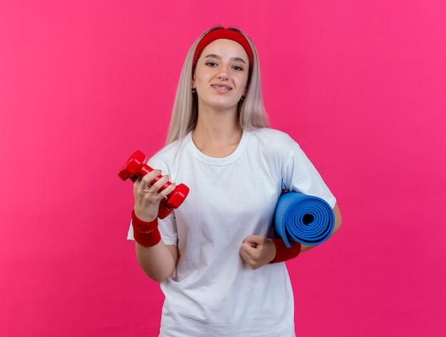머리띠와 팔찌를 착용하는 중괄호와 함께 웃는 젊은 스포티 한 여자는 분홍색 벽에 고립 된 스포츠 매트와 아령을 보유하고
