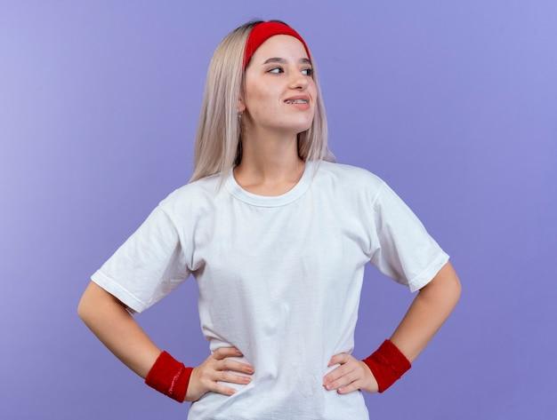 머리띠와 손목 밴드를 착용하고 허리에 손을 넣고 보라색 벽에 고립 된 측면을보고 중괄호를 착용 한 젊은 스포티 한 여자를 웃고
