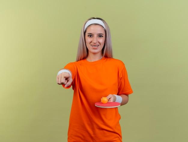 Sorridente giovane donna sportiva con bretelle che indossano fascia e braccialetti tiene la pallina da ping-pong sulla racchetta e punti nella parte anteriore isolata sulla parete verde oliva