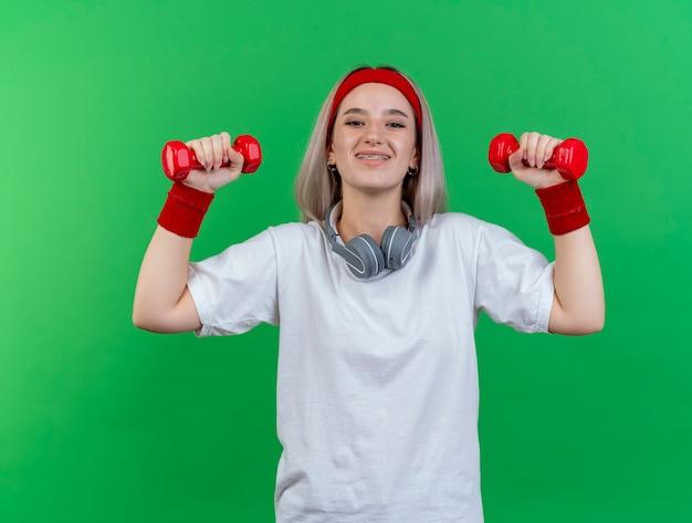 La giovane donna sportiva sorridente con le parentesi graffe che indossa la fascia e i braccialetti con le cuffie sul collo tiene i manubri isolati sulla parete verde