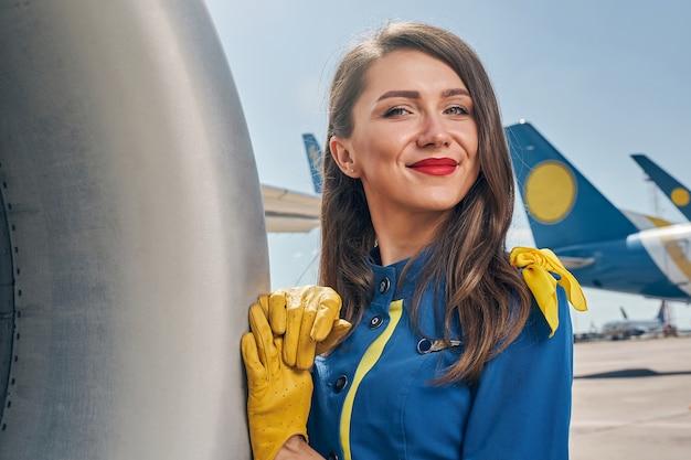 Улыбающаяся молодая стюардесса в кожаных перчатках, опираясь на фюзеляж самолета