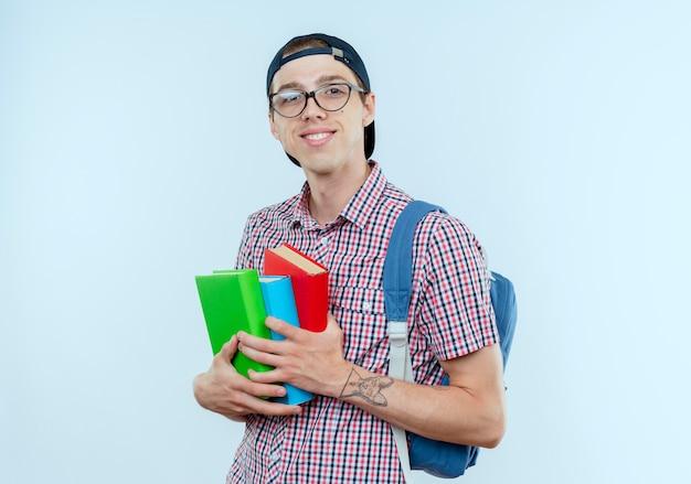 Улыбающийся молодой студент мальчик в задней сумке и очках и кепке с книгами на белом