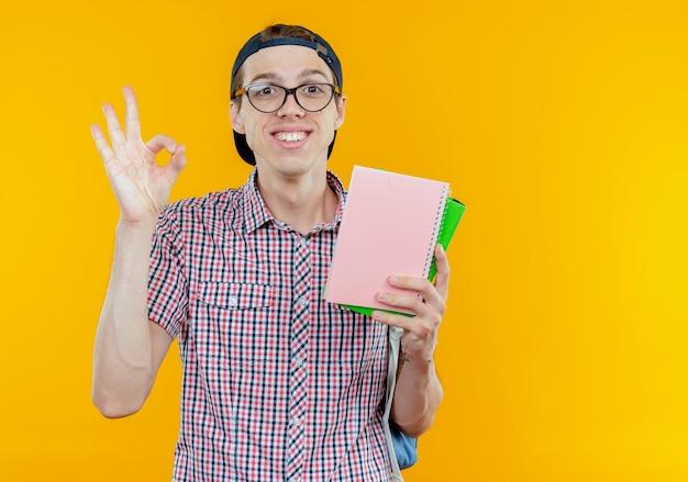 バックバッグとメガネとノートを保持し、白で大丈夫なジェスチャーを示すキャップを身に着けている若い学生の少年の笑顔