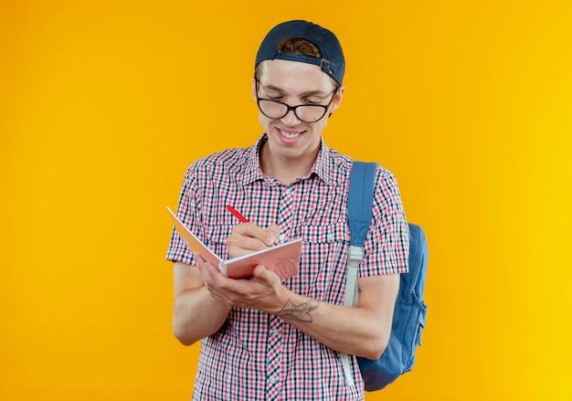 Улыбающийся молодой студент мальчик в задней сумке и очках и кепке что-то пишет в блокноте на белом