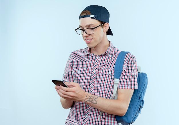 Ragazzo giovane studente sorridente che porta la borsa e gli occhiali posteriori e la tenuta della protezione e che esamina il telefono su bianco