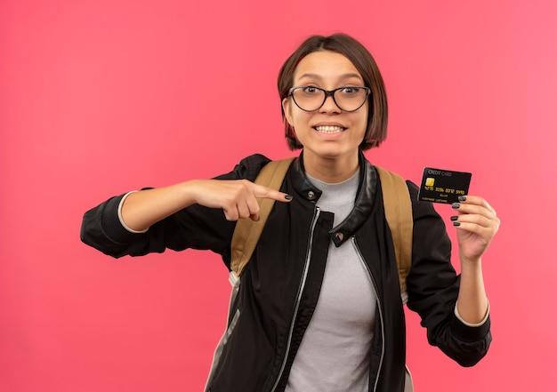 Улыбающаяся молодая студентка в очках и задней сумке держит и указывает на кредитную карту, изолированную на розовой стене